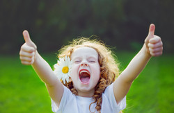 Canva - Laughing girl showing thumbs up.