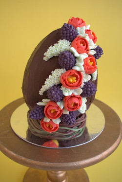 Chocolate cake easter egg filled with dulce de leche and covered with ganache and buttercream flower