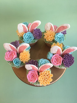 Easter cupcakes decorated with buttercream flowers and chocolate bunny ears