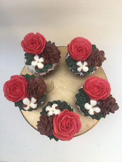 Christmas cupcakes decorated with pine cones, cotton flowers and red roses