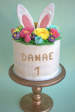Vanilla cake decorated with buttercream spring flowers and chocolate bunny ears