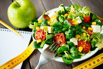 salad with an apple, notebook and tape measurer