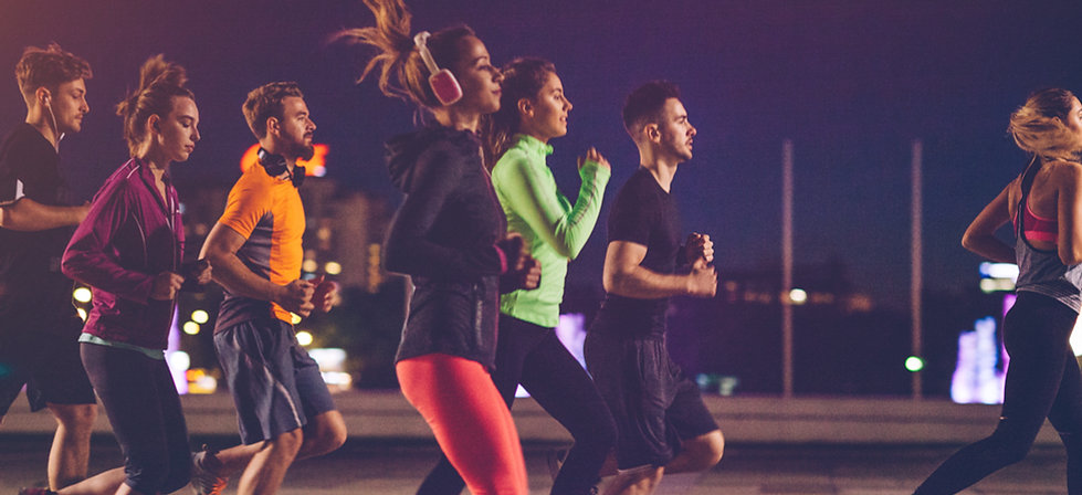 A group of runners jogging at night.