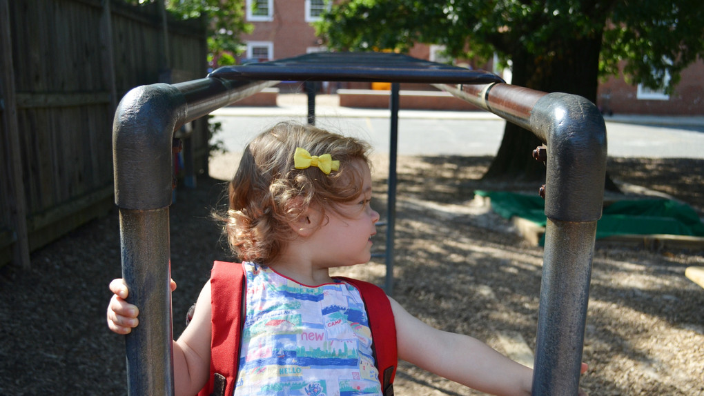 Toddler with backpack on monkey bars.jpg