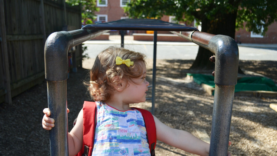 Toddler with backpack on monkey bars.jpg