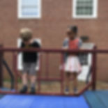 Boy and girl playing on playground.