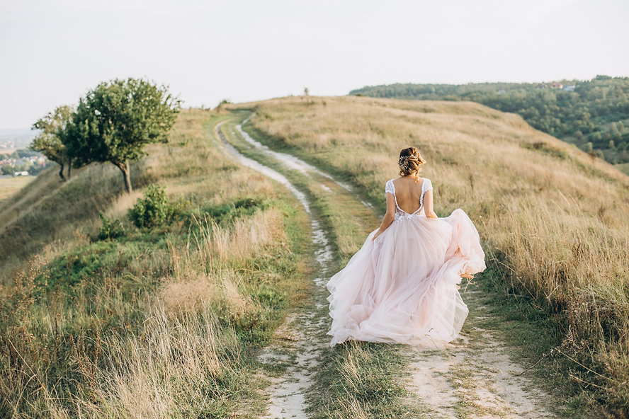 bride runs up the hill along the road an
