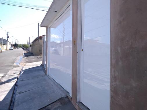 Portão basculante e social de alumínio branco fechado, sob medida.