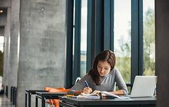 Studentin mit Buch und Laptop Bibliothek