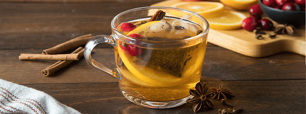 Cup of Hot Tea with Lemon Slice, Cranberries and Cinnamon sticks