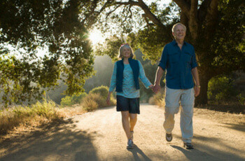 Older couple, holding hands on a walking path through nature
