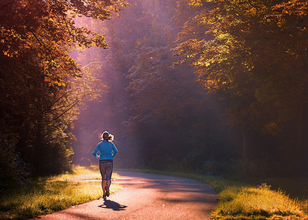 Woman running on paved path through trees with sunbeams