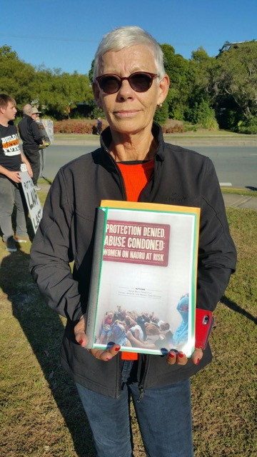 Refugee Action Collective spokesperson Amanda McNulty taking the AWSWN report to Minister Dutton's office.