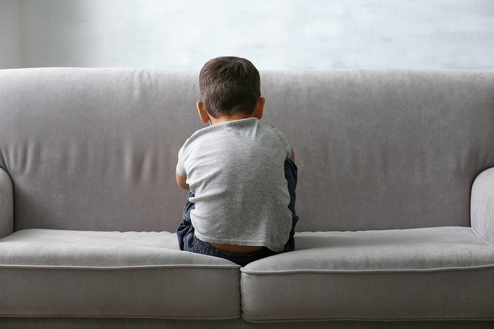 A boy sat on a grey sofa with back to the room