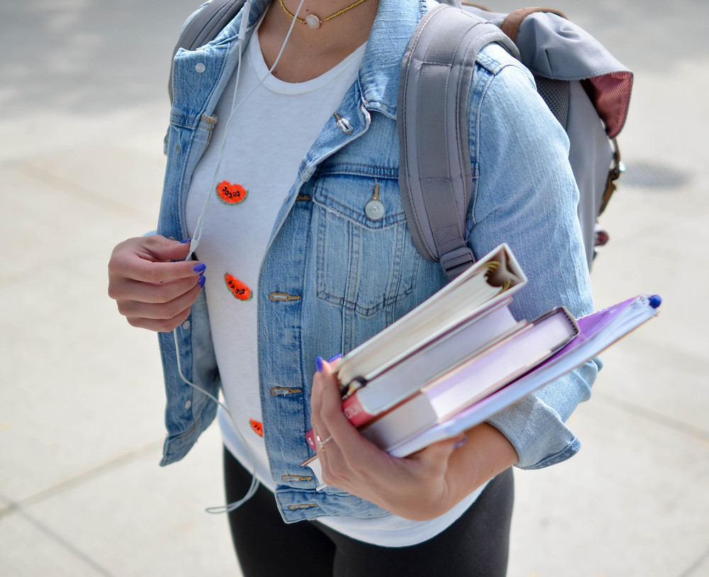 A female student holds books after completing a coaching session at The Key Clinic to help to activate her inner coach and boost her positive mindset.