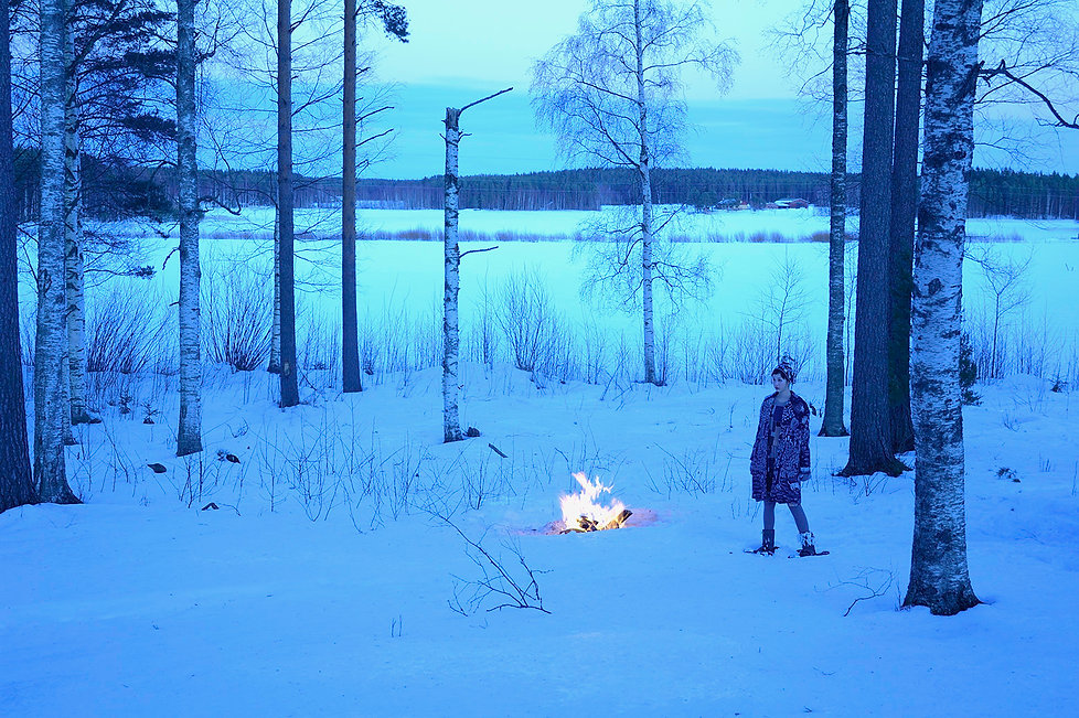 Girl watching a log fire in a snow covered forest in Finland