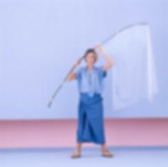 Model wearing Youji Yamamoto outfit holding a bow