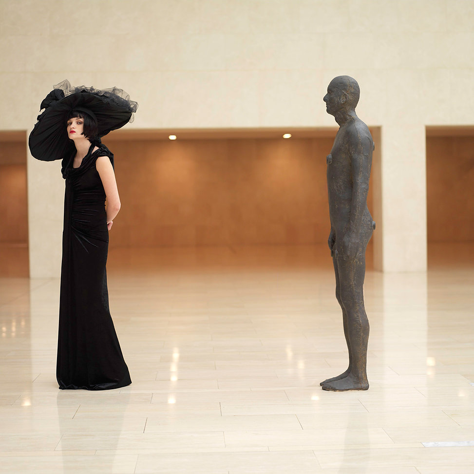 Model wearing a black dress with a huge black hat on standing by a statue of a man