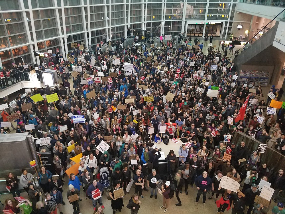 image description: Thousands pack SeaTac Airport in protest of Trump's ban on Muslim immigration.  photo credit: Alex Garland