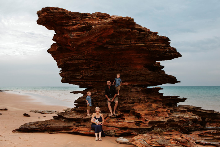 A family together on a big rock at Entrence Point in Broome