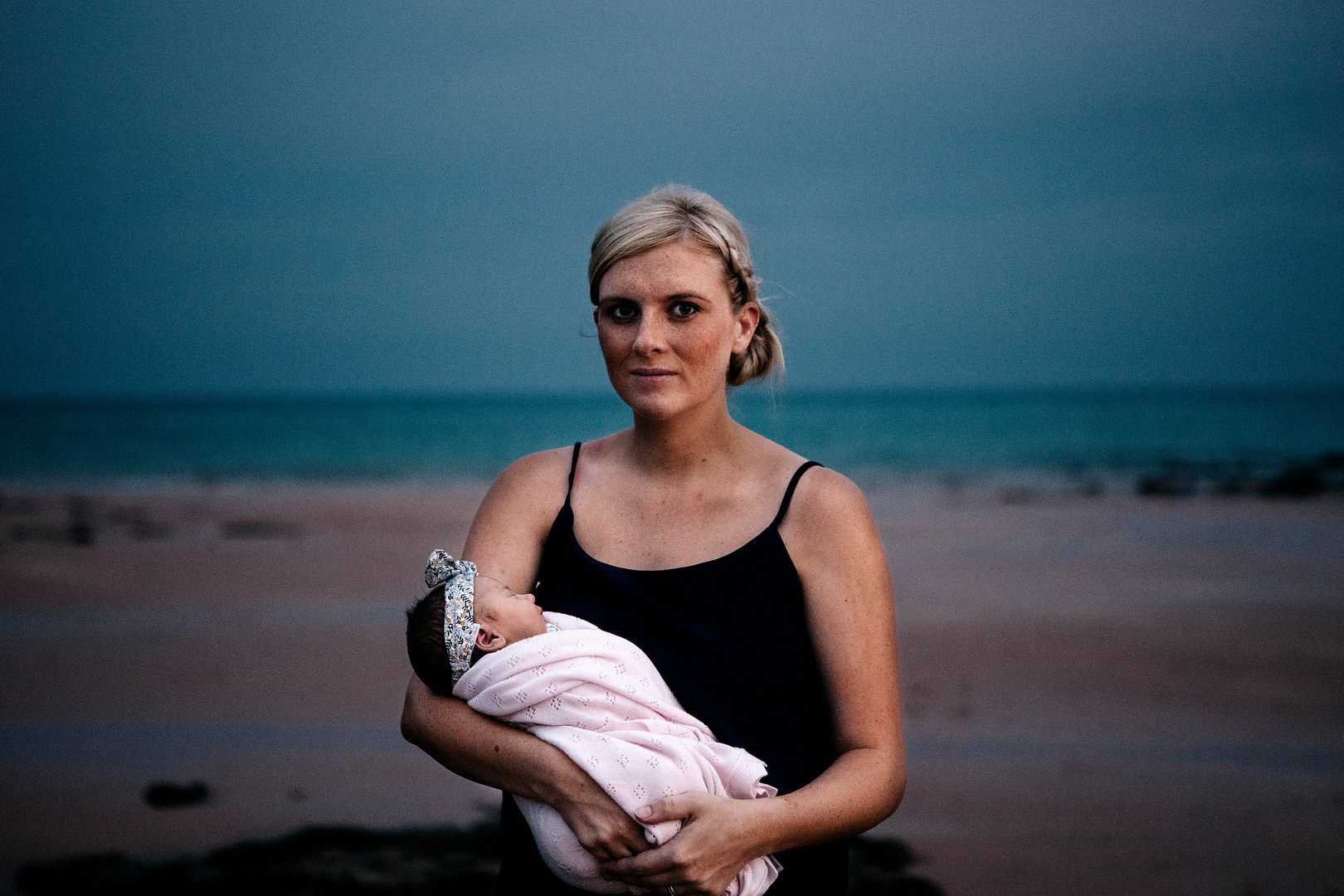 A mum holds her new born baby during sunset on a beach