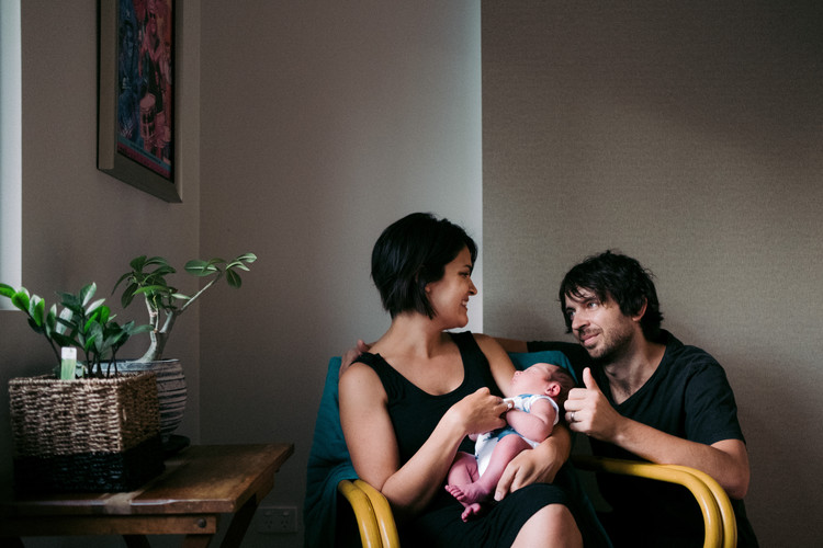 A new mum and dad look at each other with smiles as they hold their new son.
