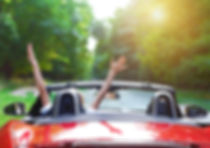Carefree DriveWoman with hands in the air in convertible car