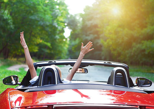 Stock photo of a white woman driving a red convertible car on a road near trees with her hands in the air happily