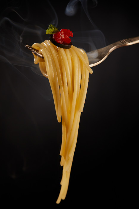 Spaghetti on a fork with smoke rising.