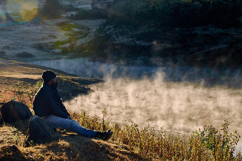 Traveller sitting by a lake with smoke rising from it early in the morning.
