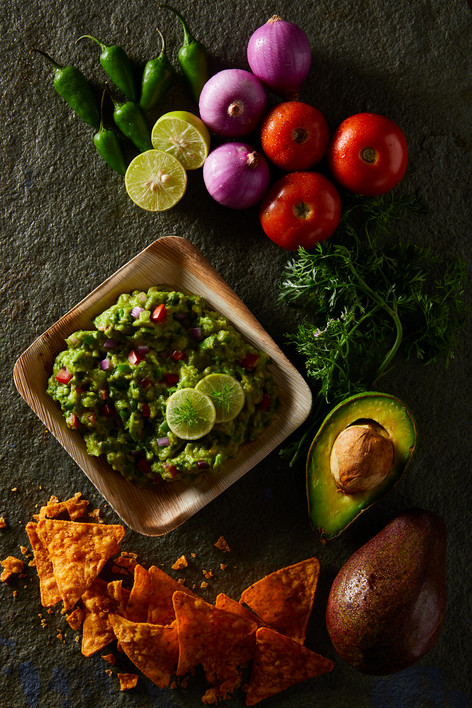 Guacomole with Chips and ingredients shown.