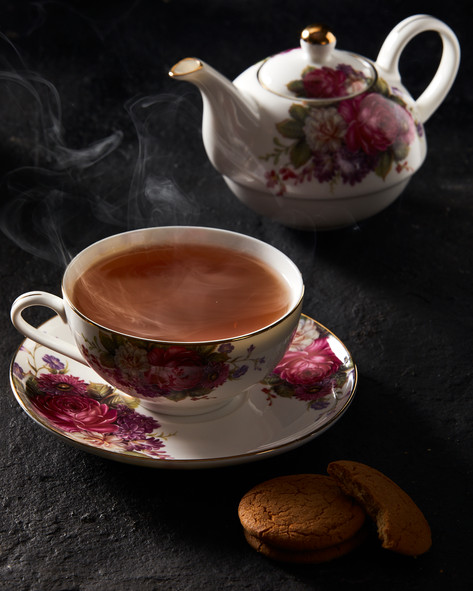 Tea with smoke rising with biscuits.