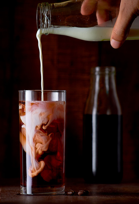 Cold coffee with milk pouring into glass.