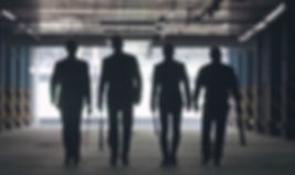 Main character's silhouettes; four shadowed men, walking in a parking garage with various weapons