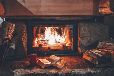 Open book by the Fireplace with Christmas ornaments. Open storybook lying on a wooden bench by the f
