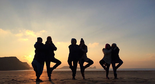 Beautiful shot from a retreat weekend: partner yoga (tree pose) at rhossili bay beach at suset.