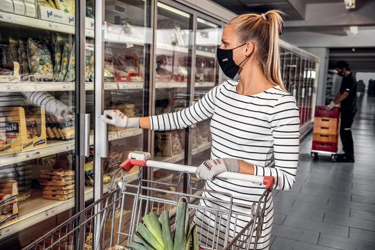 A young woman in Uvex Phynomic silv-air Covid-19 virus gloves holds a supermarket cart and opens a frozen food display cabinet door.