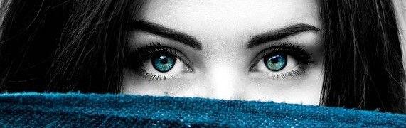 Visage d'une femme qui porte un masque pour se protéger de la Covid-19, on voit ses beaux yeux verts.