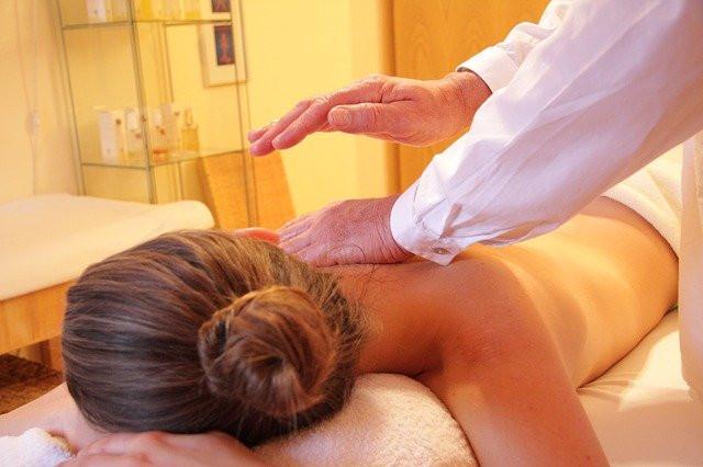 Femme allongée sur le ventre recevant des passes magnétiques d'un magnétiseur.