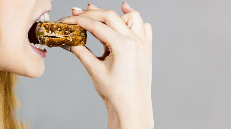 A magnetizing young woman bites with full white teeth from the food brought by her right hand.
