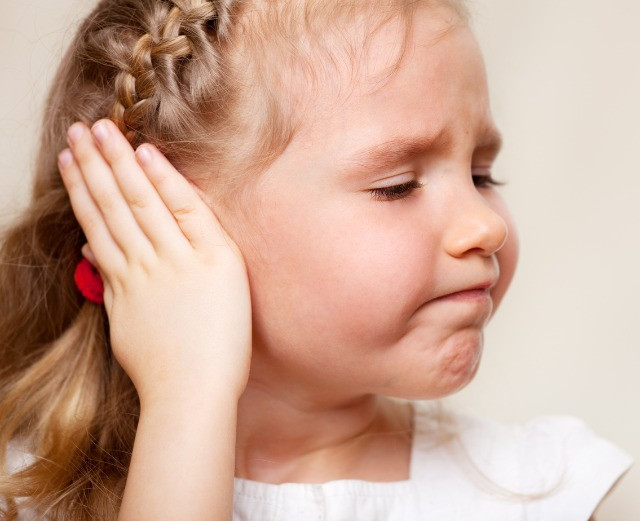 A child suffers from an ear infection and holds her right ear with her hand