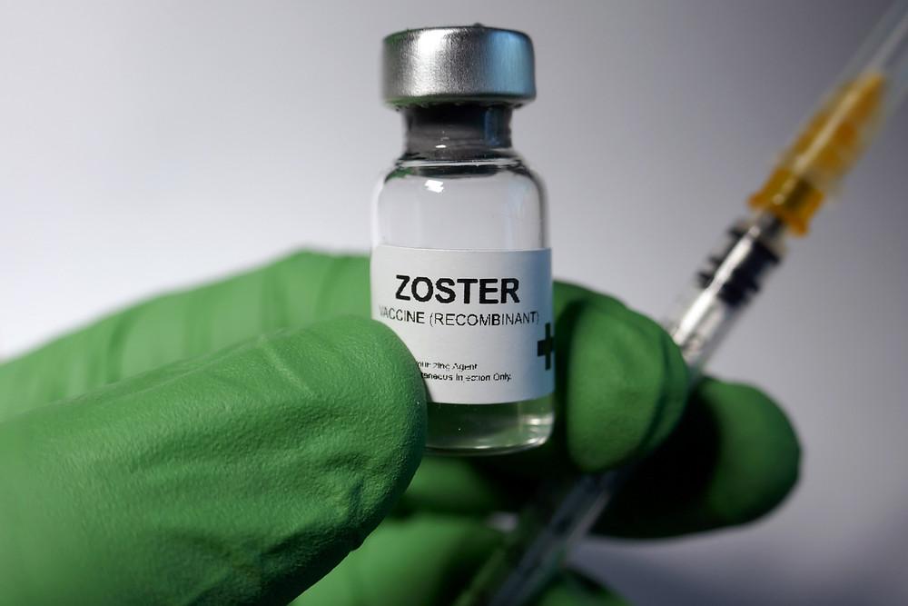 Une main gauche avec un gain vert tient une seringue et une dose de vaccin contre le zona.