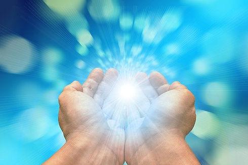 Sur un fond bleu, les mains du magnétiseur rayonnent et émettent une lumière