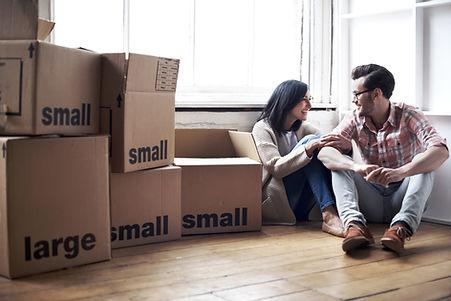 Casal de clientes ao lado de caixas para mudanças.