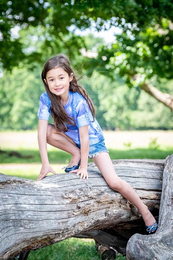 Girl climbing on log in Richmond, London