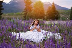 girl sitting in a field of flowers