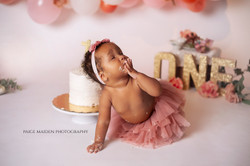 baby eating cake at a photoshoot