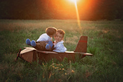 brothers playing in a wooden plane