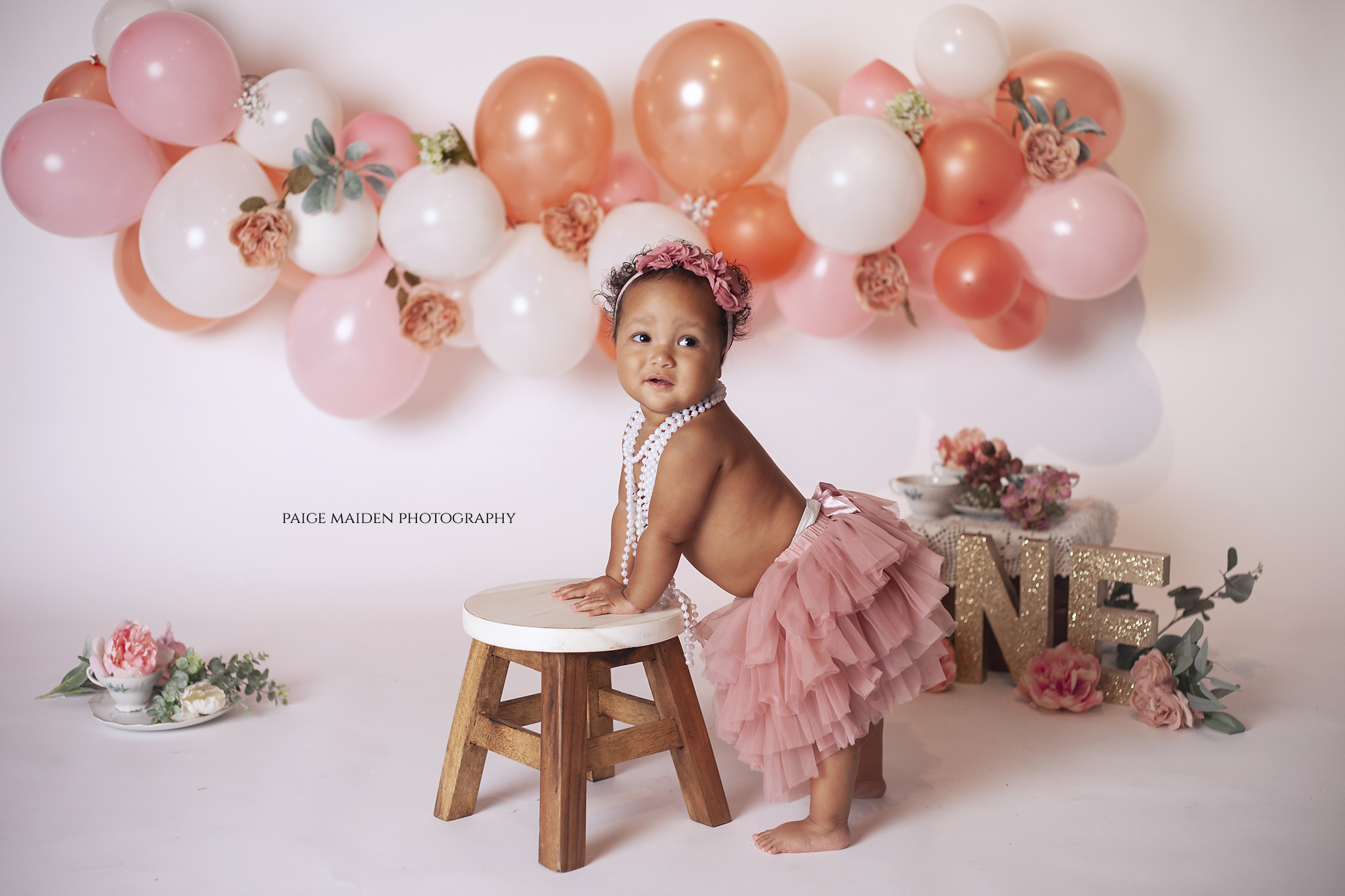 baby girl in pink tutu with stool