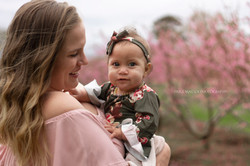 mom and baby girl with peach trees